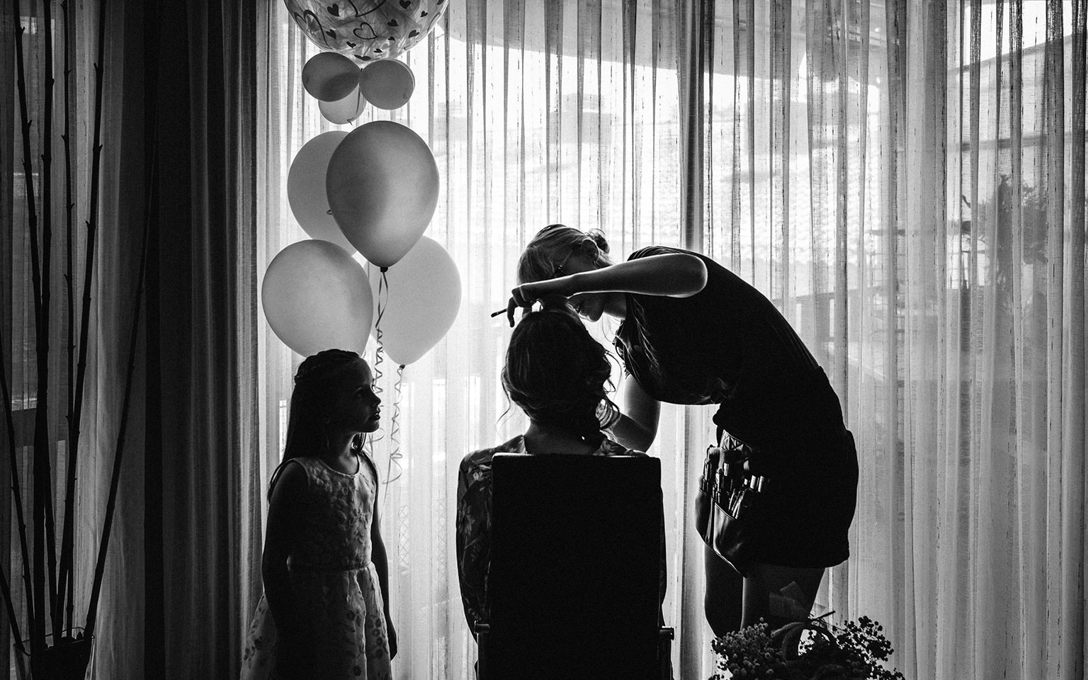 niña con globos mira como maquillan a la novia