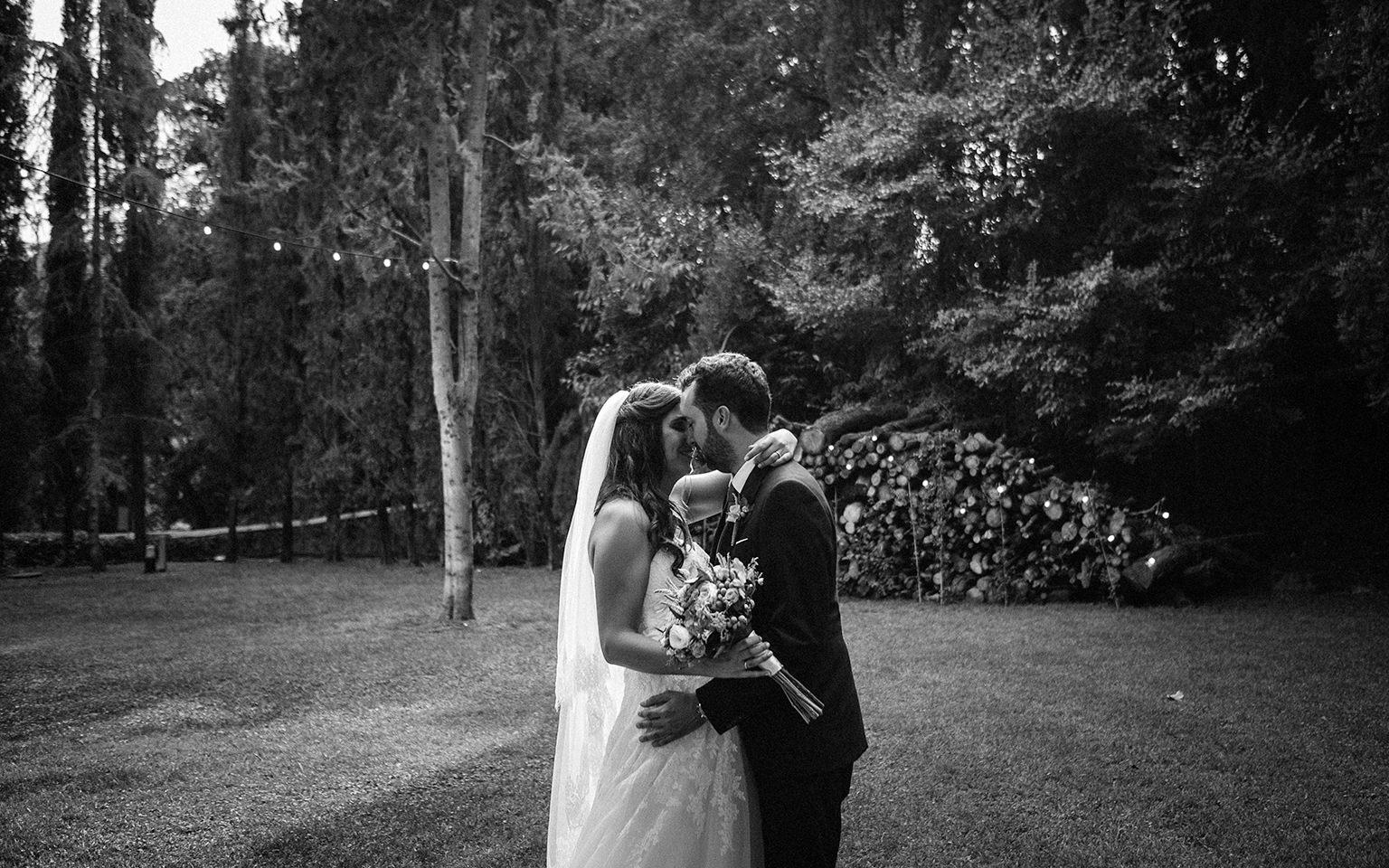 Novios abrazados se besan en el jardín